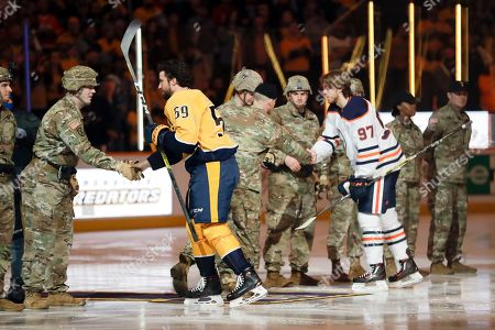 Nashville Predators captain Roman Josi (59), of Switzerland, and Edmonton Oilers captain Connor McDavid (97) greet Army soldiers from Fort Campbell, Ky., before an NHL hockey game, in Nashville, Tenn