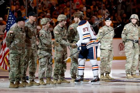 Edmonton Oilers captain Connor McDavid (97) greets Army soldiers from Fort Campbell, Ky., before an NHL hockey game between the Oilers and the Nashville Predators, in Nashville, Tenn