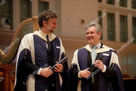 German operatic tenor Jonas Kaufmann, left, and English-Italian conductor and pianist Sir Antonio Pappano stand together on stage after being presented with their honorary Doctor of Music awards by Britain's Prince Charles at the Royal College of Music's annual awards in London