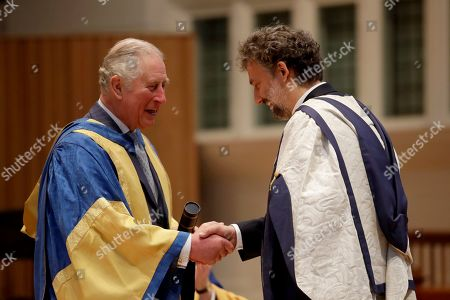 Britain's Prince Charles shakes hands as he presents German operatic tenor Jonas Kaufmann with an honorary Doctor of Music award at the Royal College of Music's annual awards in London