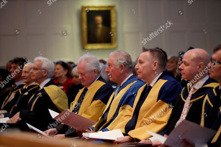Britain's Prince Charles, centre, listens to music being performed as he sits flanked by Director Professor Colin Lawson, centre left, and Chairman Lord Black of Brentwood, centre right, during the Royal College of Music's annual awards in London