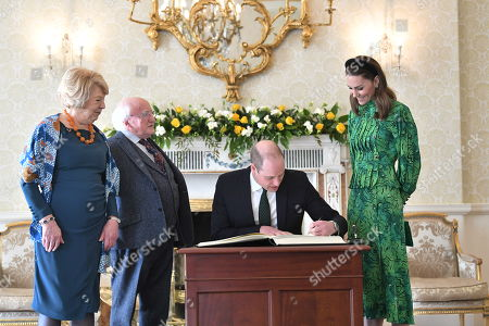 (L-R) Sabina Coyne, President of Ireland Michael D. Higgins and Catherine Duchess of Cambridge watch as Prince William signing guestbook during a meeting