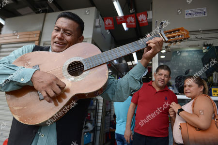 """Stock Image of Street musician Angel Alvarado, known as """"Allan El Trovador,"""" sings his """"coronavirus"""" song at a market in Guayaquil, Ecuador, . Alvarado, from Colombia, said he started improvising songs about the coronavirus that includes people's complaints about price gouging in Guayaquil, a city where several patients are being treated with for COVID-19"""