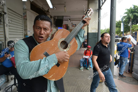 """Street musician Angel Alvarado, known as """"Allan El Trovador,"""" sings his """"coronavirus"""" song at a market in Guayaquil, Ecuador, . Alvarado, from Colombia, said he started improvising songs about the coronavirus that includes people's complaints about price gouging in Guayaquil, a city where several patients are being treated with for COVID-19"""