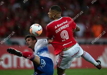Paolo Guerrero of Brazil's Internacional, right, fights for the ball with Benjamin Kuscevic of Chile's Universidad Catolica during a Copa Libertadores soccer match in Porto Alegre, Brazil