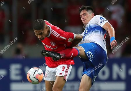 Paolo Guerrero of Brazil's Internacional, left, fights for the ball with Alfonso Parot of Chile's Universidad Catolica during a Copa Libertadores soccer match in Porto Alegre, Brazil