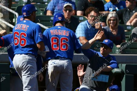 Chicago Cubs' Noel Cuevas (66) and P.J. Higgins (86) celebrate their runs scored against the Colorado Rockies with bench coach Andy Green, right, during the fourth inning of a spring training baseball game, in Scottsdale, Ariz