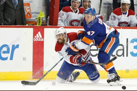 Stock Image of Leo Komaraov, Shea Weber. New York Islanders right wing Leo Komarov (47) defends against Montreal Canadiens defenseman Shea Weber (6) during the first period of an NHL hockey game, in New York
