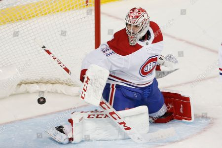 Montreal Canadiens goaltender Carey Price turns the puck away during the second period of the team's NHL hockey game against the New York Islanders, in New York