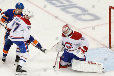 Carey Price, Brett Kulak, Derick Brassard. Montreal Canadiens goaltender Carey Price (31) makes a save with defenseman Brett Kulak (77) fending off New York Islanders center Derick Brassard in front of the crease during the third period of an NHL hockey game, in New York
