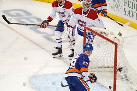 Carey Price, Brock Nelson. Montreal Canadiens goaltender Carey Price (31) watches as New York Islanders center Brock Nelson (29) flicks the puck into the vacant net for a goal during the third period of an NHL hockey game, in New York. The Canadiens won 6-2