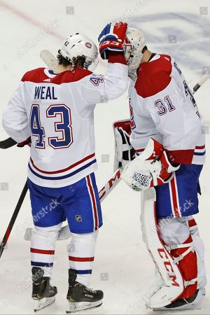Jordan Weal, Carey Price. Montreal Canadiens center Jordan Weal (43) celebrates with goaltender Carey Price (31) after the team's NHL hockey game against the New York Islanders, in New York. The Canadiens won 6-2