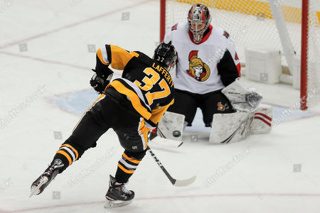 Pittsburgh Penguins' Sam Lafferty has his shot stopped by Ottawa Senators goaltender Craig Anderson during the third period of an NHL hockey game, in Pittsburgh. The Penguins won 7-3