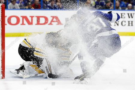Stock Picture of Boston Bruins goaltender Tuukka Rask (40) gets covered in ice by Tampa Bay Lightning center Yanni Gourde (37) during the second period of an NHL hockey game, in Tampa, Fla