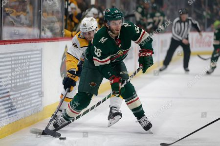 Minnesota Wild right wing Ryan Hartman (38) is defended by Nashville Predators center Colton Sissons (10) during the first period of an NHL hockey game, in St. Paul, Minn