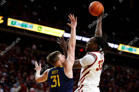 Iowa State forward Solomon Young, right, shoots over West Virginia forward Logan Routt during the first half of an NCAA college basketball game, in Ames, Iowa