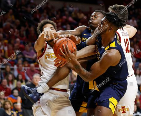 Iowa State forwards George Conditt, left, and Michael Jacobson, right, battle West Virginia forwards Oscar Tshiebwe and Derek Culver, second from right, for a rebound during the second half of an NCAA college basketball game, in Ames, Iowa. West Virginia won 77-71