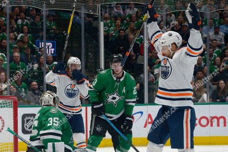 Edmonton Oilers right wing Alex Chiasson, right, and center Connor McDavid (97) celebrate a goal as Dallas Stars goaltender Anton Khudobin (35) and defenseman Esa Lindell (23) react during the second period of an NHL hockey game in Dallas