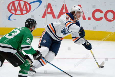 Edmonton Oilers center Connor McDavid (97) controls the puck next to Dallas Stars defenseman Esa Lindell (23) during the second period of an NHL hockey game in Dallas