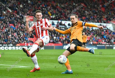 Jackson Irvine of Hull City crosses as Jordan Thompson of Stoke City blocks