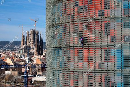 French urban climber, Alain Robert, right, scales the 144 meters (472 ft) of the Glories tower with the La Sagrada Familia Basilica designed by architect Antoni Gaudi in the background, left, in Barcelona, Spain, . Robert, known as Spiderman climbed up 144 meters of the Glories tower, previously known the Agbar tower in around 20 minutes. Spanish authorities briefly detained him after the stunt