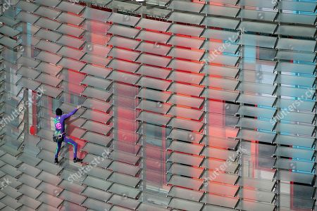 French urban climber, Alain Robert, left, scales the 144 meters (472 ft) of the Glories tower with the La Sagrada Familia Basilica designed by architect Antoni Gaudi in the background, left, in Barcelona, Spain, . Robert, known as Spiderman climbed up 144 meters of the Glories tower, previously known the Agbar tower in around 20 minutes. Spanish authorities briefly detained him after the stunt