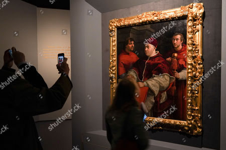 People look at Raphael's Portrait of Pope Leo X with cardinals Giulio De'Medici and Luigi de'Rossi, in Rome, . The paintings, drawings and sketches in the most ambitious assemblage ever of Raphael works in an exhibition, more than even the Renaissance superstar had in his workshop at one time, are collectively insured for 4 billion euros ($.4 billion), against the likes of theft or vandalism. But no money can guarantee that Italy's outbreak of coronavirus, the largest in Europe, won't play havoc with the three-month run in Rome of the art world's eagerly-awaited blockbuster