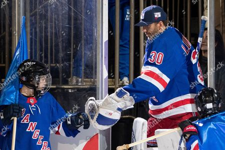 Stock Picture of New York Rangers goaltender Henrik Lundqvist high fives a child as he arrives on the ice before the start of an NHL hockey game against the St. Louis Blues, at Madison Square Garden in New York
