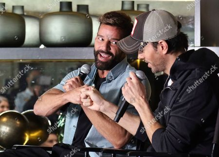 Stock Picture of Enrique Iglesias, Ricky Martin. Ricky Martin, left, and Enrique Iglesias fist bump as they speak at the Enrique Iglesias and Ricky Martin Press Conference at The London West Hollywood Hotel, in West Hollywood, Calif