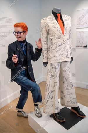 Stock Image of Sandy Powell with the autographed outfit which is to be auctioned