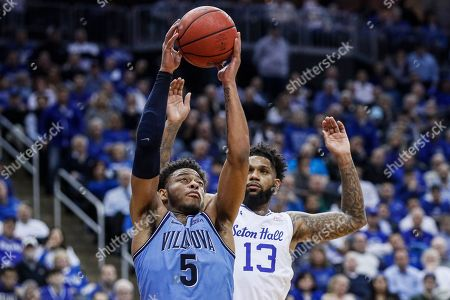 Stock Picture of Justin Moore, Myles Powell. Villanova's Justin Moore (5) rebounds against Seton Hall's Myles Powell (13) during the second half of the team's NCAA college basketball game, in Newark, N.J