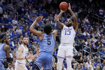 Myles Powell, Justin Moore. Seton Hall's Myles Powell (13) shoots over Villanova's Justin Moore (5) during the second half of an NCAA college basketball game, in Newark, N.J