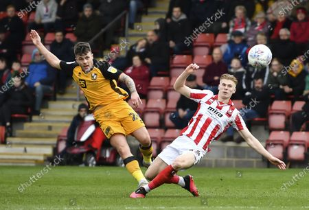 Stock Picture of Mitchell Clark of Port Vale with a shot on goal under pressure from Max Sheaf of Cheltenham Town