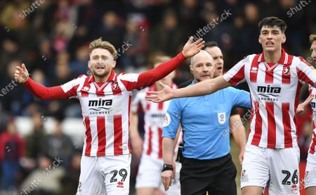 Alfie May of Cheltenham Town and Jacob Greaves of Cheltenham Town react after Scott Duncan match referee awards a penalty that is overruled by his assistant