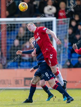 Stock Image of George Edmundson of Rangers beats Lee Erwin of Ross County in the air.