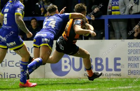 Callum Turner of Castleford runs to the line but is caught by the neck by Keanan Brand of Warrington Wolves and is given a penalty try to bring Castleford 2 points ahead