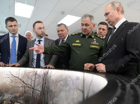 From right: Russian President Vladimir Putin, Minister of Defense of Russia Sergey Shoygu, Governor of the Pskov Region Mikhail Vedernikov and Deputy Prime Minister of Russia Yuri Borisov view the model of panorama of the 6th parachute company battle in cultural and leisure center.