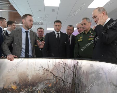 Russian President Vladimir Putin (right), Minister of Defense of Russia Sergey Shoygu (second from right), Governor of the Pskov Region Mikhail Vedernikov (center) and Deputy Prime Minister of Russia Yuri Borisov (fourth from right) view the model of panorama of the 6th parachute company battle in cultural and leisure center.