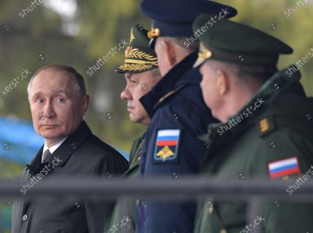 Russian President Vladimir Putin (left) and Minister of Defense of Russia Sergey Shoygu (second from left) review the troops of the 104th Krasnoznamensky guards parachute regiment of the 76-th Airborne division near the Kupol memorial sign dedicated to the soldiers of the 6th parachute company in Cherekha village as part of the events commemorating the soldiers of the 6th parachute company, who died bravely during a clash with militia in Argun Gorge in 2000.