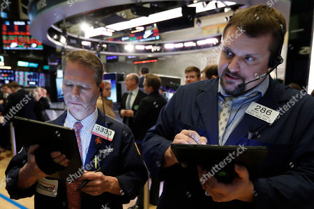 Stock Image of Robert Charmak, Michael Milano. Traders Robert Charmak, left, and Michael Milano work on the floor of the New York Stock Exchange, . Stocks are opening sharply lower on Wall Street, erasing 2% from major indexes, a day after surging 4% as the mood swings back to fear about the effects of a fast-spreading virus