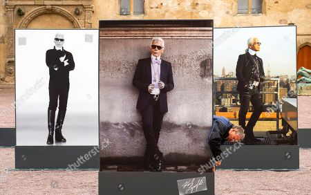 A worker fixes pillars with Lagerfeld portraits during the press preview of the exhibition 'Karl Lagerfeld Photography. The retrospective.' in the Moritzburg Art Museum in Halle (Saale), Germany, . The exposition brings together more than 400 photographs of the German creative director, fashion designer, artist, photographer, and caricaturist who lived in Paris and died last year. The exhibition starts on March 8, 2020 and lasts until Aug. 23, 2020