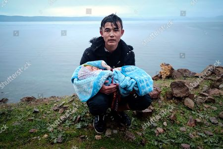 A migrant holding a baby pauses on the side of the road while walking to the village of Skala Sikaminias, on the Greek island of Lesbos, after crossing on a dinghy the Aegean sea from Turkey on . Turkey said Thursday it would deploy special forces along its land border with Greece to prevent Greek authorities from pushing back migrants trying to cross into Europe, after Turkey declared its previously guarded gateways to Europe open