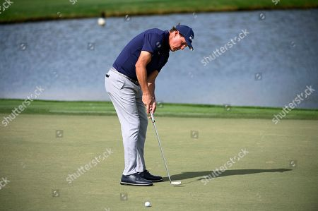 Stock Photo of Phil Mickelson watches his putt on the eighth green during the first round of the Arnold Palmer Invitational golf tournament, in Orlando, Fla