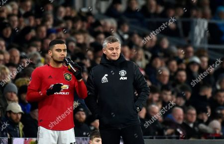 Manchester United's manager Ole Gunnar Solskjaer, right, gives instructions to Manchester United's Andreas Pereira during the FA Cup fifth round soccer match between Derby County and Manchester United at Pride Park in Derby, England