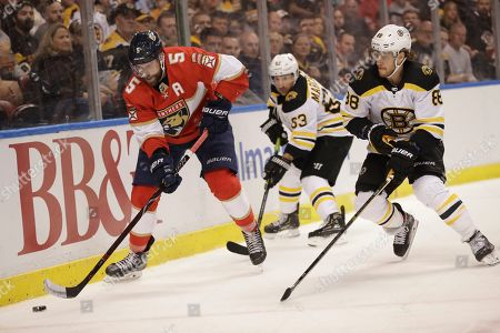 Stock Image of Florida Panthers defenseman Aaron Ekblad (5) keeps the puck away from Boston Bruins right wing David Pastrnak (88) and left wing Brad Marchand (63) during the first period of an NHL hockey game, in Sunrise, Fla