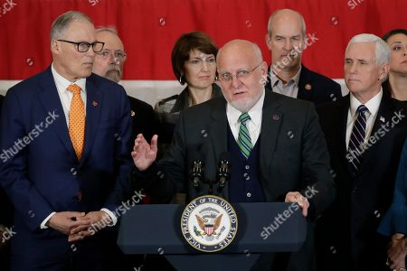 Dr. Robert Redfield, center, Director of the Centers for Disease Control and Prevention, speaks as Gov. Jay Inslee, left, and Vice President Mike Pence, right, look, during a news conference at Camp Murray in Washington state. Pence was in Washington to discuss the state's efforts to fight the spread of the COVID-19 coronavirus