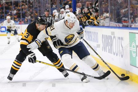Buffalo Sabres forward Kyle Okposo (21) carries the puck past Pittsburgh Penguins defenseman Jack Johnson (3) during the first period of an NHL hockey game, in Buffalo, N.Y