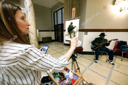 """Stock Photo of Bluesman McKinney Williams, Susan Patton. Susan Patton uses a cell phone photograph of """"Bluesman"""" McKinney Williams as her in hand model while putting the finishing touches to her oil painting as he plays in the rotunda of the Capitol in Jackson, Miss., . The Mississippi Arts Commission's annual Arts Day at the Capitol brought a variety of performance, musical, visual artists and supporting organizations to mingle with lawmakers and stress the importance of the arts as both entertainment and educational"""