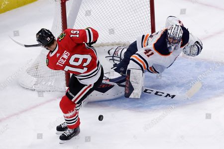 Mike Smith, Jonathan Toews. Edmonton Oilers goalie Mike Smith, right, blocks a shot by Chicago Blackhawks center Jonathan Toews during the first period of an NHL hockey game in Chicago