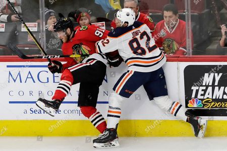 Drake Caggiula, Caleb Jones. Chicago Blackhawks center Drake Caggiula, left, is checked by Edmonton Oilers defenseman Caleb Jones during the first period of an NHL hockey game in Chicago